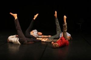 četri cilvēki guļ uz grīdas ar paceltu kāju
